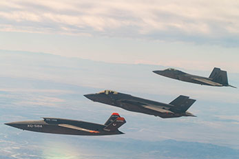 XQ-58 Valkyrie flying in formation with F-22 Raptor and F-35A Lightning II